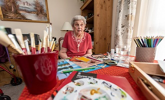 Elderly woman at table with paint brushes