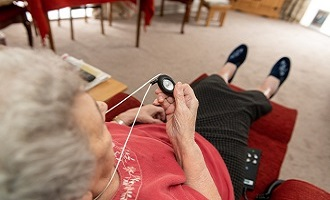 Elderly woman holding personal alarm
